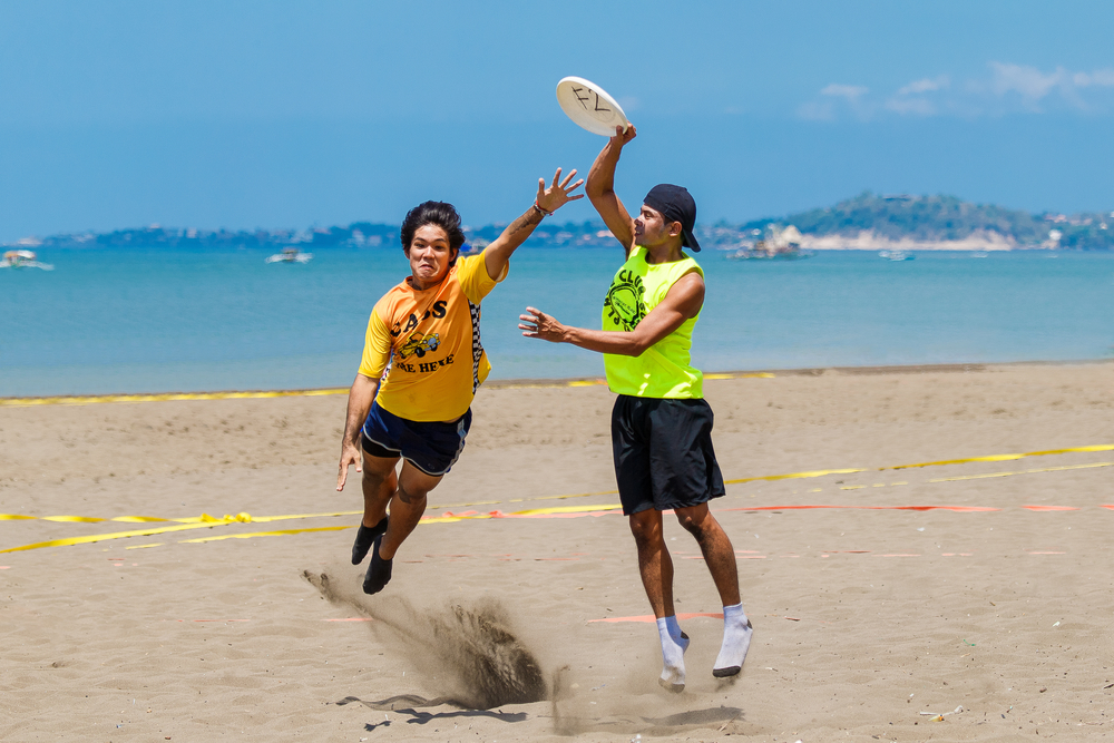 ultimate frisbee players in the sand