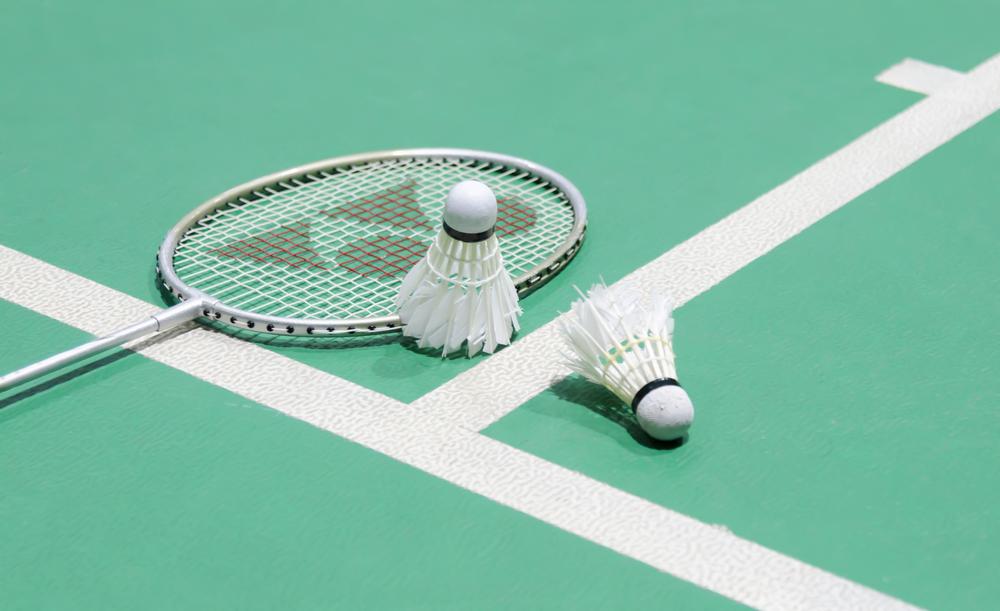 badminton racket and shuttlecocks on court