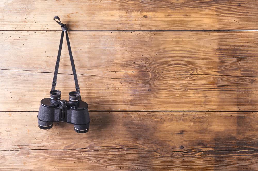 binoculars hanging on wooden fence