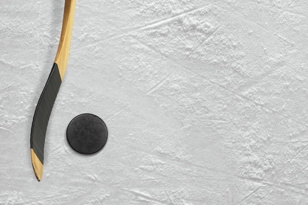 hockey stick on ice with puck